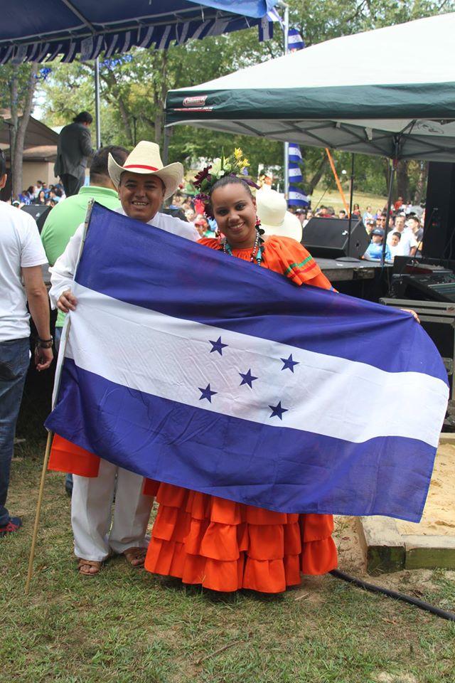 Nuestros compatriotas mostrando con orgullo la bandera de Honduras.