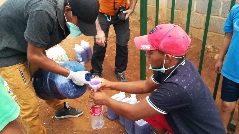 Las personas llevan recipientes para recibir los productos de limpieza.